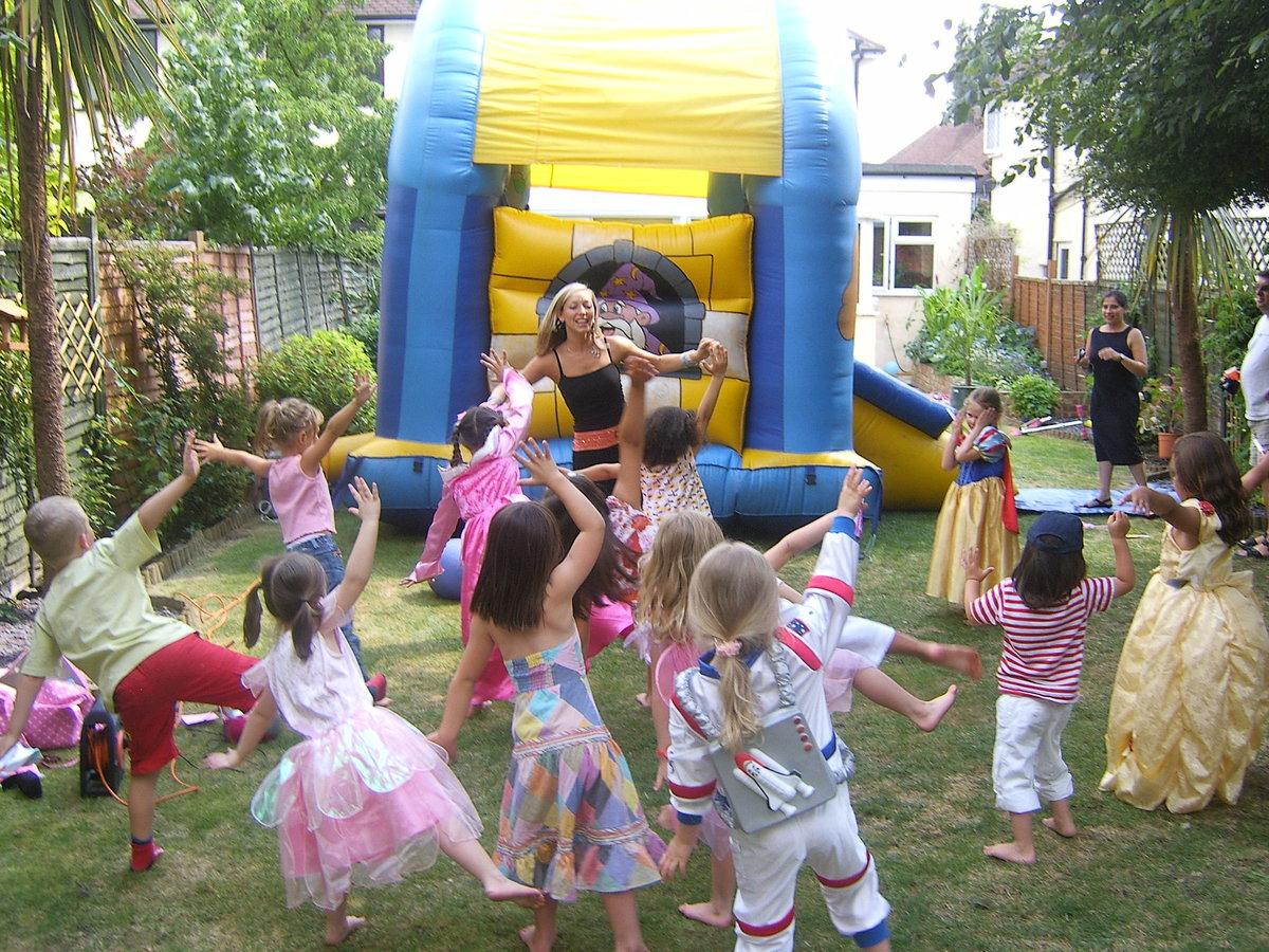 Children dancing in front of a bouncy castle