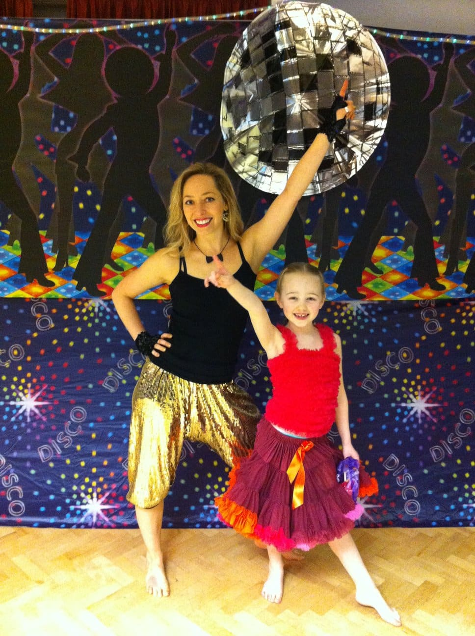 Olivia and birthday girl posing with a big disco ball