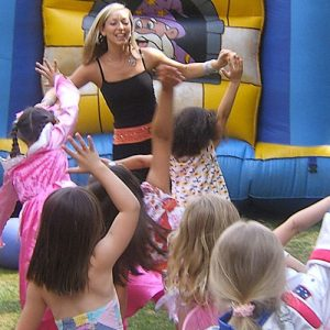 Children in fancy dress dancing infront of a bouncy castle