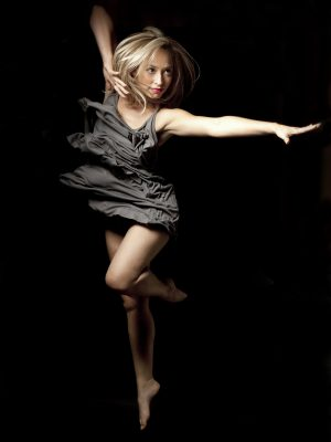 Dancer in a grey dress jumping in the air