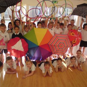 Children holding hoops and umbrellas